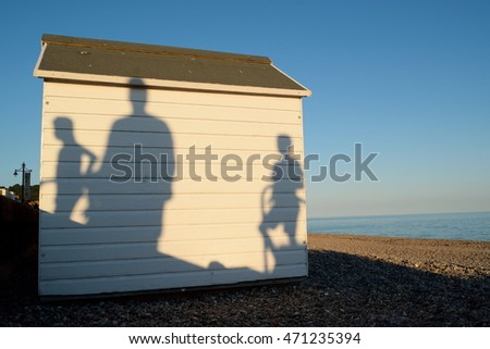 White wooden beach hut with shadows of the people walk in Seaton, England