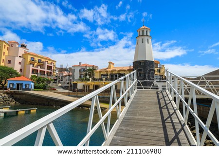 White wooden bridge to lighthouse in marina with colorful houses of Portuguese village, Madeira island, Portugal  - stock photo