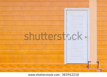 white wooden door and the orange wall with copyspace
