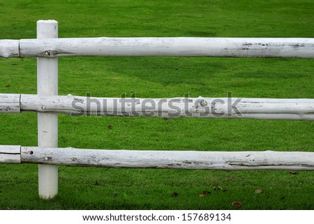 White wooden fence and green grass field