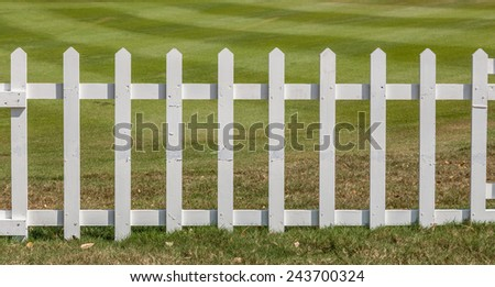 White wooden fence in farm field marks for land property.  - stock photo