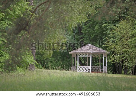 white wooden gazebo on a background of green trees in summer Park