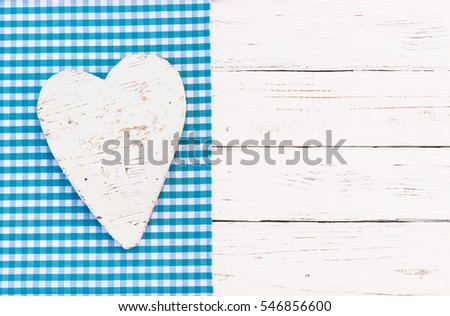 White wooden heart shape on rustic blue checkered fabric and white wood background, top view, copy space.