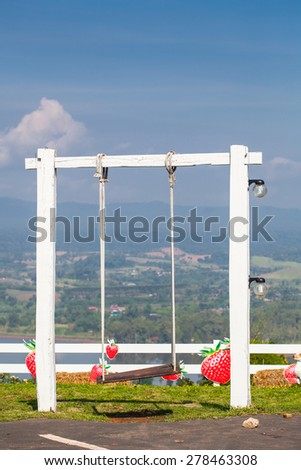 White wooden swing hanging by a nylon rope on a hilltop viewpoint on a clear day. - stock photo