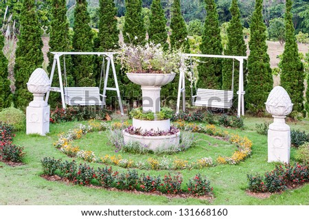 White wooden swing in the English style garden of country house. - stock photo