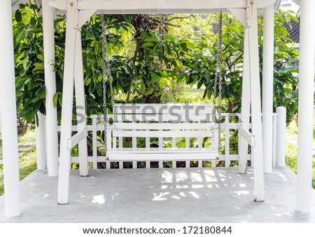 White wooden swing in the garden  - stock photo