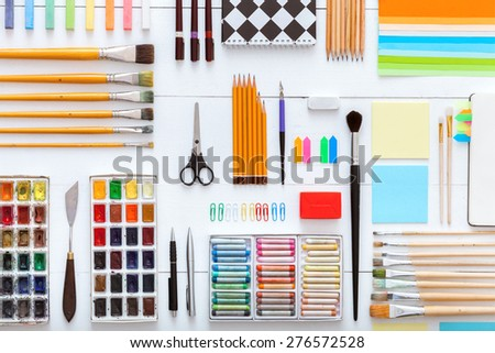 White, wooden table top view of the artist. On the table are perfect subjects for art, pencils, paints, crayons, colored paper, scissors, Stationery items. Designed for easy operation. - stock photo