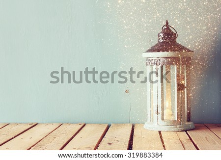white wooden vintage lantern with burning candle and tree branches on wooden table. retro filtered image with glitter overlay  - stock photo