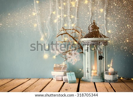 white wooden vintage lantern with burning candle christmas gifts and tree branches on wooden table. retro filtered image with glitter overlay  - stock photo