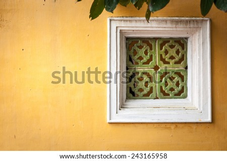 White wooden window with ornate green framing on wall of yellow stucco. Some green leaves over old worn window. House exterior in Vietnam, architecture of Asia. - stock photo