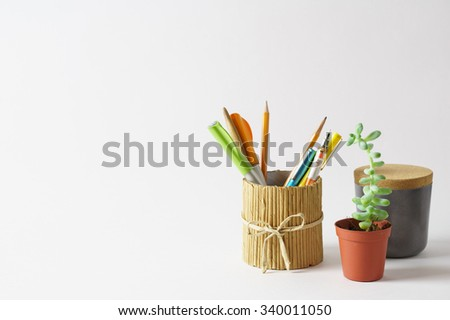 White workplace with pencil holders, succulent plant and drawing tools