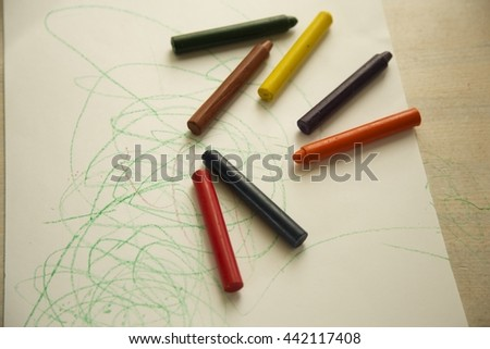 White workspace with kids colored pencils on wooden table and abstract kids picture