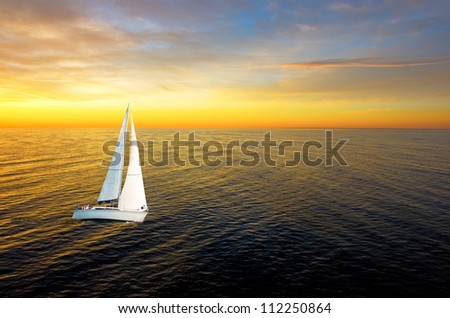 White yacht at golden sunset with wide horizon