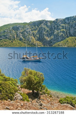 white yacht in Hisaronu bay, Aegean sea,  near Camellia island rocky bank with trees and plants on sunny day, Turkey - stock photo