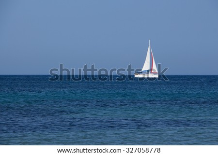 White yacht traveling with sails down on blue sea and sky horizon  - stock photo