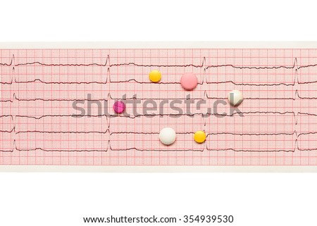 White, yellow and pink tablets on paper ECG results isolated on white background. Clipping path included.  - stock photo