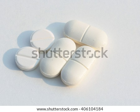 white Yellow green tablet pills capsules on white background - stock photo