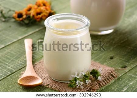 white yogurt in glass jar on green table for breakfast - stock photo
