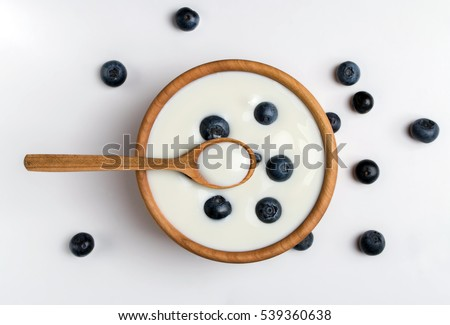 White yogurt in natural wooden bowl with blueberries. Top view.