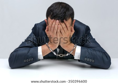 White young businessman handcuffed. He is sitting at a table with face between his palms showing guilt and frustration - stock photo