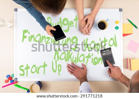 whiteboard with german words for start up, budget, calculation, business plan - stock photo