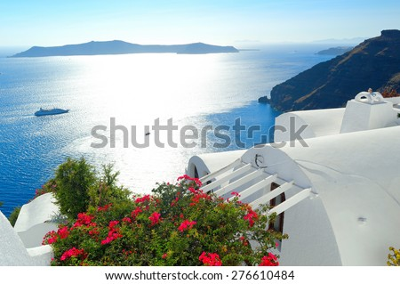 Whitewashed cycladic rooftops with blooming flowers and romantic view of sunset over volcanic caldera, Santorini, Cyclades, Greece - stock photo