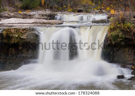 Whitewater cascades down the limestone ledges of Indiana's Upper Cataract Falls in early autumn. - stock photo