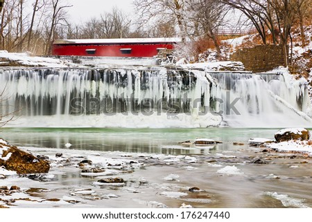Whitewater flows over icicles at a frozen Upper Cataract Falls with a red covered bridge upstream. Photographed on Mill Creek near Cloverdale, Indiana. - stock photo