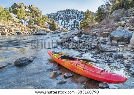 whitewater kayak with a paddle on a river shore  - Arkansas River, Colorado in winter scenery - stock photo