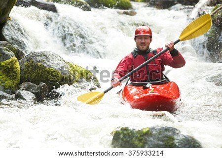 whitewater kayaker in a creek - stock photo