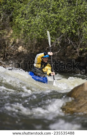 Whitewater Kayaker Navigating Rapid - stock photo