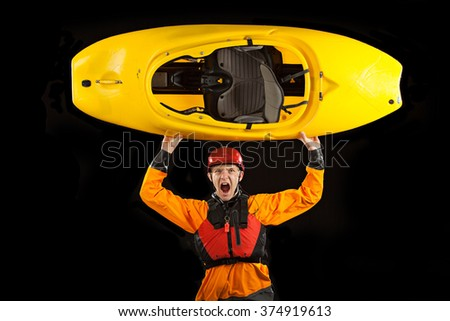 Whitewater kayaker on black background holding boat over his head