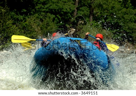 whitewater river raft exploding into the air off wave
