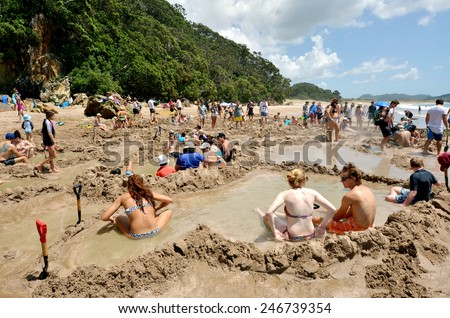 WHITIANGA, NZL - Jan 20 2015:Visitors making small hot water pools in Hot Water beach.it one of the most popular geothermal attractions in New Zealand, about 700,000 people visit the beach annually. - stock photo