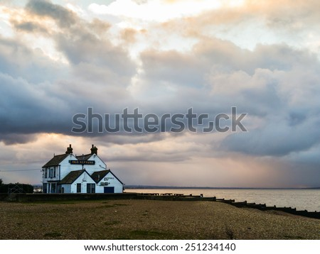 WHITSTABLE, UK - FEB 5, 2015: Storm clouds gather over the 'Old Neptune' pub in Whitstable. The Old Neptune was rebuilt in 1897 after a great storm destroyed the previous building.  - stock photo