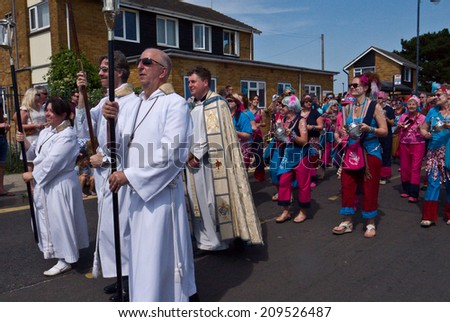WHITSTABLE,UK-JULY 26: The Rev Simon Tillotson and clergy from St Peters  take part in the Whitstable Oyster Festival Parade, after the Blessing of the Oysters. July 26, 2014 Whitstable UK.