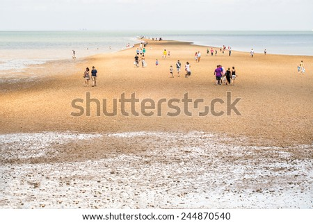 "WHITSTABLE, UK - JUNE 30, 2013 Tourists and locals walk on a spit of land out to sea, it is a popular attraction and only visible at low tide. It is referred to locally as ""The Street"". - stock photo"