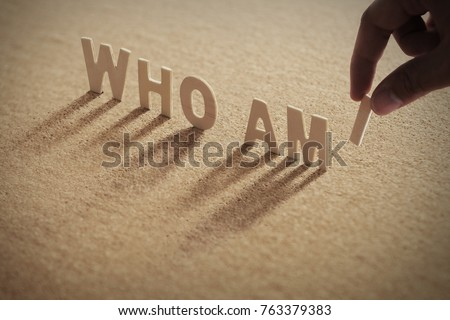 WHO AM I wood word on compressed or corkboard with human's finger at I letter.