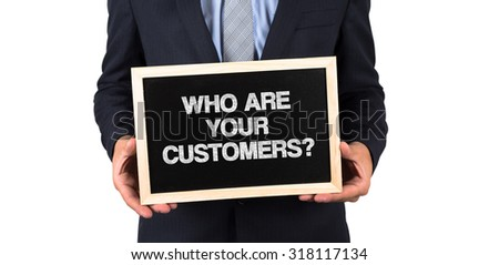 Who Are Your Customers? written on a Chalkboard in Businessman Hands - stock photo