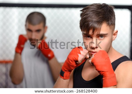 Who is stronger. Portrait of fearless fighters in a fighting cage waiting for their next opponent - stock photo