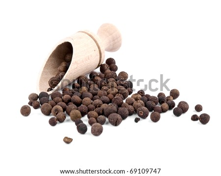 Whole allspice berries  and wooden shovel on white background - stock photo