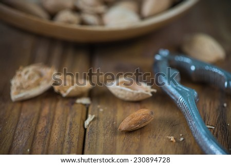Whole almonds and nut crusher on wooden table - stock photo