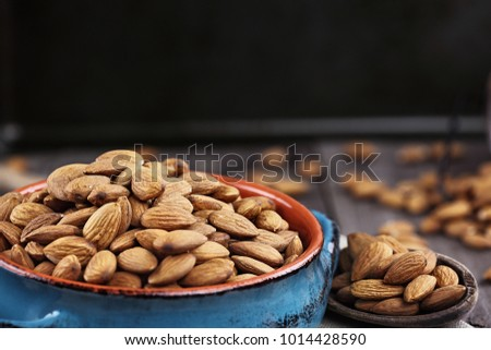 Whole almonds in bowl and wooden spoon against a rustic background.