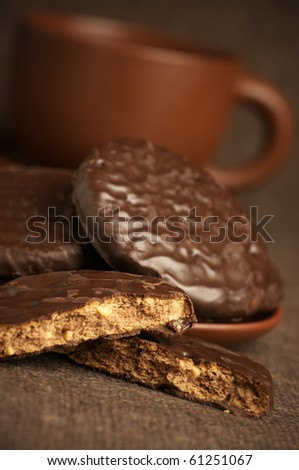 Whole and break chocolate cookies with cup of coffee on brown canvas.