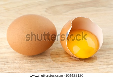 Whole and broken eggs on table - stock photo
