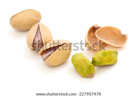 Whole and broken pistachios isolated on white background. - stock photo