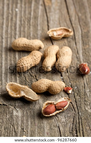 Whole and chopped peanut on old wooden table