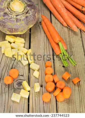 whole and diced winter root crops  against aged wooden background