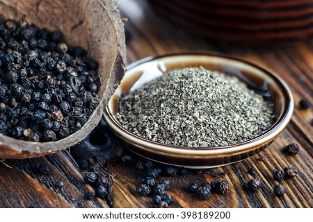 Whole and Ground black Peppercorns on old wooden table. Peppercorn Varieties. Milled black pepper. Black pepper corns and Black pepper Powder on wooden background. Close up, soft focus.  - stock photo