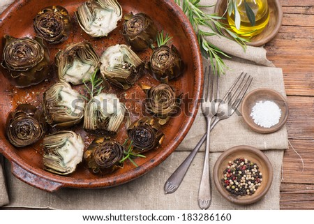 Whole and half  artichokes roasted simply, served with olive oil,  pepper and salt on the  wooden table. - stock photo